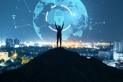 Businessman on backlit hill holding abstract polygon globe hologram on illuminated night city background. Polygonal network, safety, science, communication, programming and earth concept