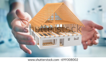 Businessman on blurred background holding 3D rendering unfinished plan house in his hand #699308002