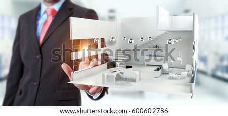 Businessman on blurred background touching white 3D rendering apartment with his finger #600602786