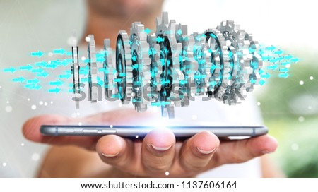 Businessman on blurred background using floating gear icons over phone 3D rendering