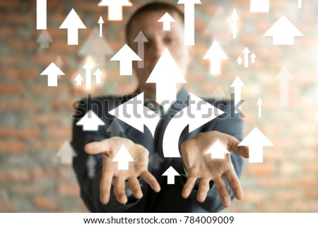 Businessman on blurred background using virtual screen giving and choice arrows icon in his hands. Directions of the company's development. ストックフォト ©