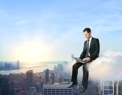 Businessman on cloud using laptop computer on city background. Cloud computing concept