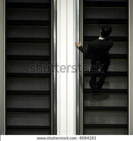 businessman on escalator with mobile
