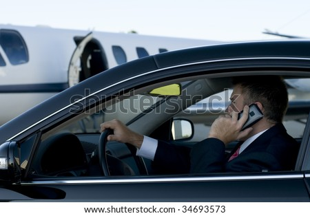 Businessman on his cell phone in his luxury car in front of a corporate jet