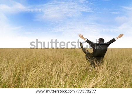 Businessman on his office chair with his arms and feet up in the air. Shot outdoor in marshes