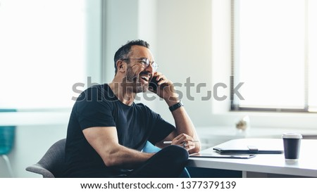 Businessman on mobile phone while working at office. Man sitting at his desk talking on mobile phone and laughing.