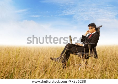 Businessman on office chair working with a laptop outdoor