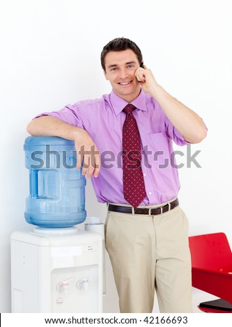 Businessman on phone by the watercooler in the office