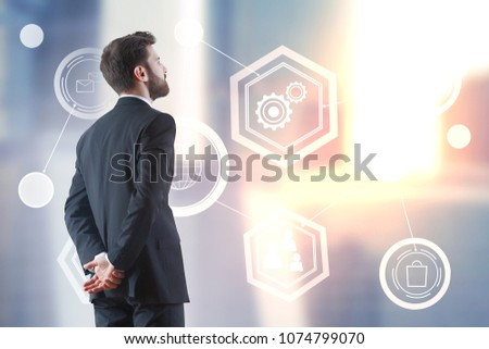 Businessman on rooftop looking at bright digital business projection. Blurry city background. Innovation and network concept  #1074799070