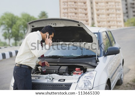 Businessman on the phone looking under the car hood
