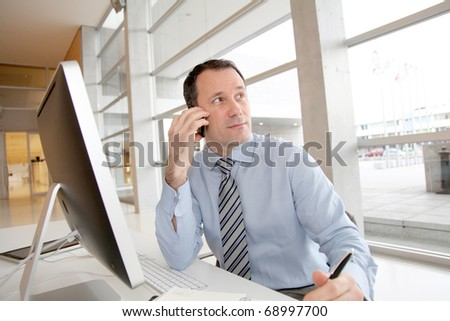 Businessman on the phone writing on agenda