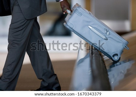 Businessman on trip taking suitcase from airport baggage carousel