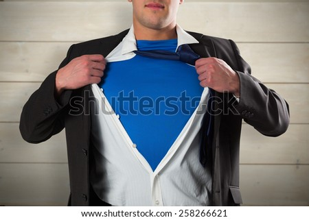 Businessman opening his shirt superhero style against bleached wooden planks background