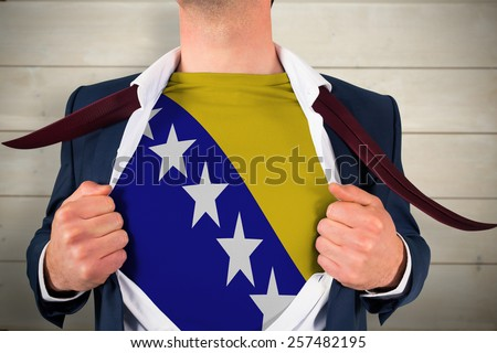 Businessman opening shirt to reveal bosnia flag against bleached wooden planks background