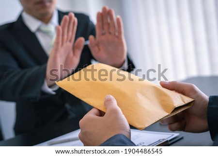 Businessman or accountant is rejecting and resisting partner bribery deals in joint financial settlement, illegal anti-bribery ideas. In work Сток-фото ©