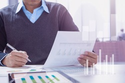 Businessman or accountant working in the office reviewing financial statements for business performace periodically.