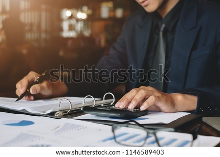 Businessman or Accountant working with calculator for investigation of corruption account. Anti Bribery concept.