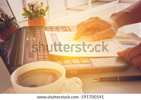 Businessman or CEO or CFO seriously analyses a company financial reports on his table. Financial reports are set of documents prepared by an administrative team at the end of an accounting period.