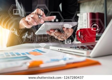 businessman or Designer using tablet with laptop and document on desk in modern office with virtual interface graphic icons network diagram.