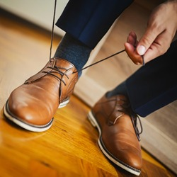 Businessman or groom tied a shoelace on his brown shoes. Shallow depth of field.
