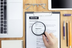 Businessman or HR Manager review a resume on his desk with Magnifier, computer laptop, digital tablet, calculator and glasses. Resume information with magnifier. Flat lay.