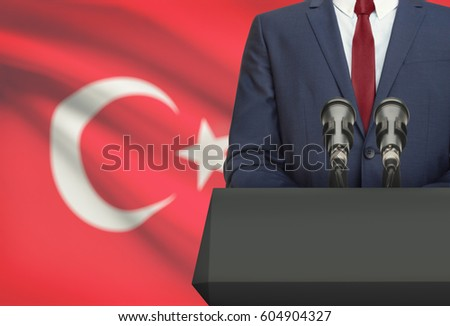 Businessman or politician making speech from behind the pulpit with national flag on background - Turkey