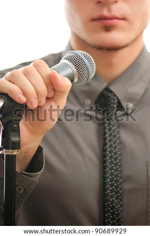 businessman or singer in grey coat witn neck tie holding microphone in his hand ready to perform - shallow DOF with focus on the microphone
