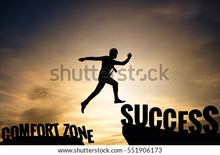 Businessman or worker jumping from Comfort zone to be Success. Business concept with sunset background.