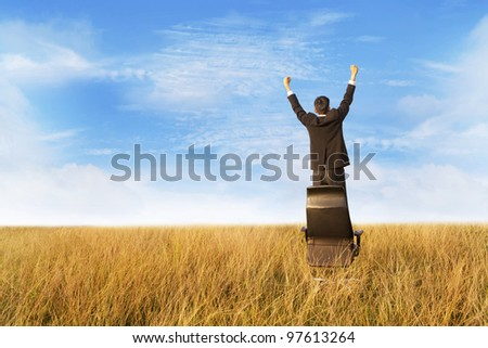 Businessman outdoor expressing his  freedom and success standing on chair