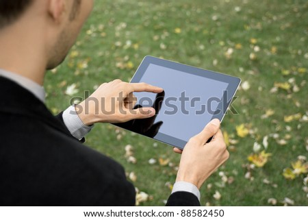 Businessman outdoors working with touch screen device.