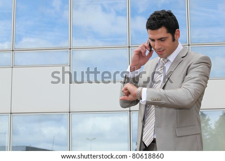 Businessman outside looking at watch