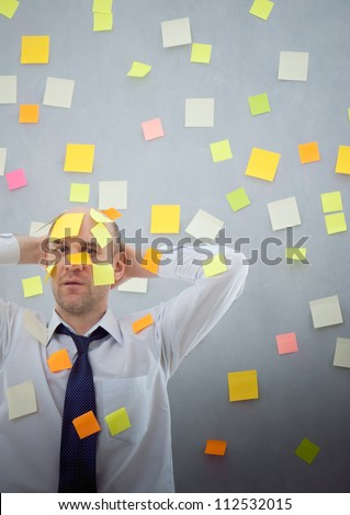 businessman overwhelmed with notes