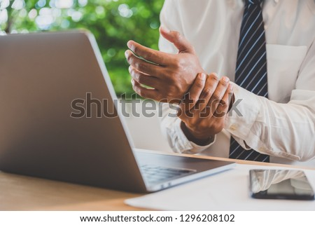 Businessman pain in hands while woking with laptop. Office syndrome concept. Сток-фото ©