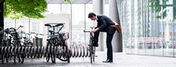 Businessman parking his bicycle in town at a bicycle rack after commuting to work in a concept of eco-friendly transport and healthy active lifestyle, panoramic banner view