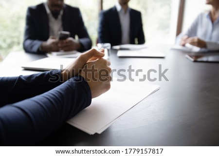 Businessman participates in business meeting, put his hands on table while listens and thinks over speaker speech, close up folded arms. Negotiation appointment in boardroom. Take part in talk concept