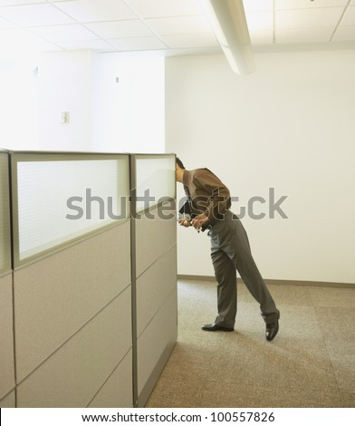 Businessman peeking around cubicle wall