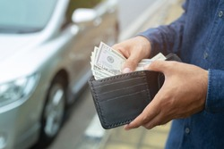 Businessman Person holding a wallet in the hands of take money out of pocket stand front car prepare pay by installments - insurance, loan and buying car finance concept insurance, payment a car