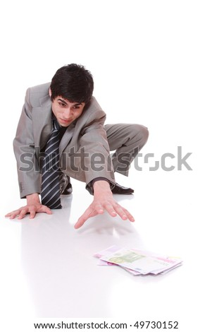 Businessman picking money on the floor over white background selective focus - stock photo