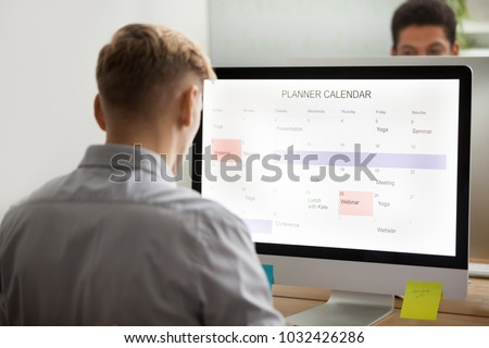 Businessman planning his day making event schedule on computer planner application in office, man using digital organizer or calendar application on desktop screen, time management concept, rear view