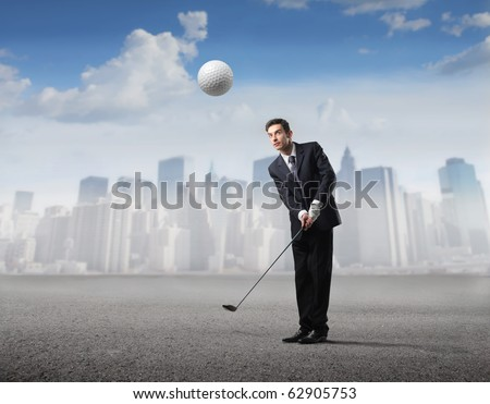 Businessman playing golf with cityscape on the background - stock photo