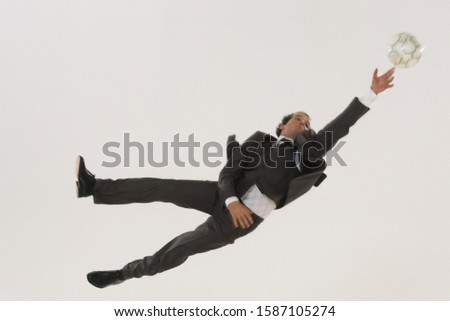 Businessman playing keeper reaching for the soccer ball in mid-air
