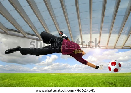 Businessman playing soccer outdoors in a green field