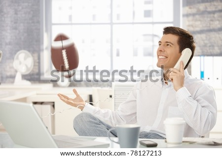 Businessman playing with football office while on landline call, laughing.?