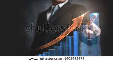 Businessman pointing arrow graph and chart, corporate growth plan or business development to success and growing growth concept