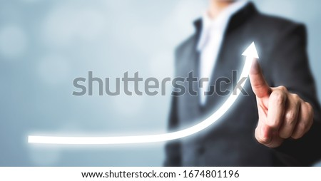 Businessman pointing arrow graph corporate future growth plan. Business development to success and growing annual revenue growth concept