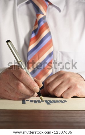 Businessman pointing at a bar chart with a pen on a desk.