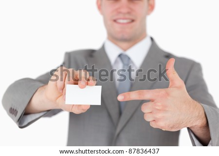 Businessman pointing at a blank business card against a white background