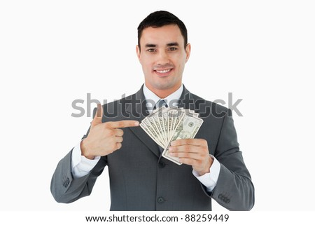 Businessman pointing at bank notes in his hand against a white background