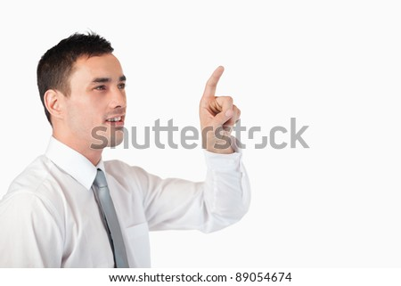 Businessman pointing at invisible screen against a white background
