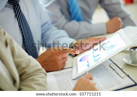 Businessman pointing at the screen of the touchpad with digital charts and graphs